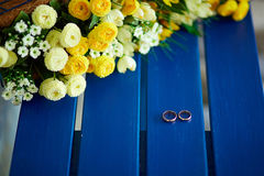 Two wedding rings. Lie on a blue shop near yellow flowers Stock Photo