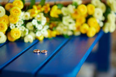 Two wedding rings. Lie on a blue shop near yellow flowers Royalty Free Stock Photography