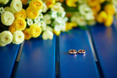 Two wedding rings. Lie on a blue shop near yellow flowers Royalty Free Stock Image