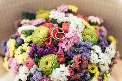 Two wedding rings lie on a bouquet of dried flowers. Two gold wedding rings lie on a wedding bouquet of dried flowers Stock Image