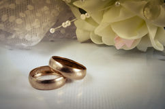 Two wedding rings lie on a light horizontal surface Stock Image