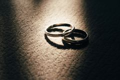 Two wedding rings lie next to the carpeting, and the ray of light illuminates them.  stock images