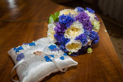 Two  wedding rings lie on the pillow,  a bouquet of blue, white and purple flowers. Royalty Free Stock Photos