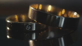 Wedding rings on dark background. Two wedding rings lie on the table on a dark background, one diamond ring, close-up stock video footage