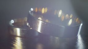 Wedding rings on dark background. Two wedding rings lie on the table on a dark background, playing with light, close-up stock footage