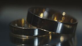 Wedding rings on dark background. Two wedding rings lie on the table on a dark background, playing with light, close-up stock video