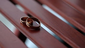 Two wedding rings lie on wooden table in day time. stock footage