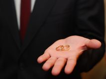 Two wedding rings, man's palm Royalty Free Stock Photography