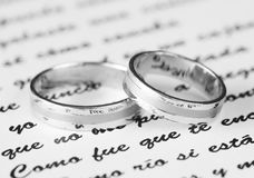 Wedding Rings. Two wedding rings lying on a Spanish text Royalty Free Stock Images