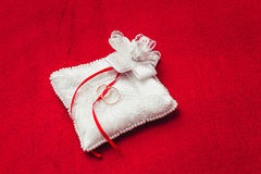 Two wedding rings on pillow on red Stock Photo
