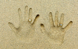 Two wedding rings placed on fingers in the sand. Two Hand shapes in the sand. Each hand has a  golden wedding ring on the fourth finger Stock Image