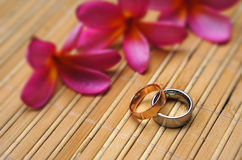 Two wedding rings and plumeria flowers. On bamboo mat Royalty Free Stock Photos