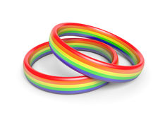 Two wedding rings with rainbow flag colors, a symbol of gay or same sex partnerships. Pair of marriage rings bearing the rainbow flag colors that symbolize gay Stock Photo