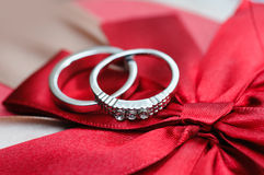Two wedding rings on red background Royalty Free Stock Image