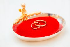 Two wedding rings on a red base with an angel.  Stock Photo