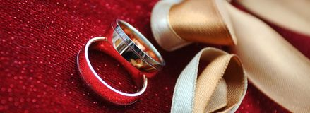 Two wedding rings on a red pillow. Two golden wedding rings on a red shiny pillow yellow bow close up, wedding day especial event concept, copyspace for text stock photography