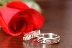 Two wedding rings with a red rose on a table Stock Photo