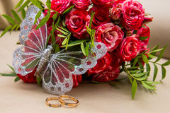 Two wedding rings, red roses. Arsenie butterfly. Royalty Free Stock Photography