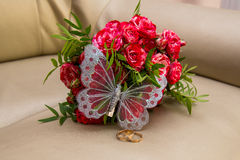 Two wedding rings, red roses. Arsenie butterfly. Royalty Free Stock Photo