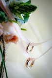 Two wedding rings on a ribbon. A pair of gold wedding rings is hanging on a pink ribbon over a bunch of flowers Stock Photos