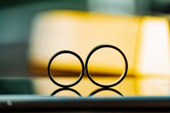 Two wedding rings are in the room on the background of light. Gold rings in the form of eight are intended for the bride and groom royalty free stock photography
