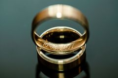 Two wedding rings on shiny surface. Two gold inscription wedding rings on shiny clean surface Royalty Free Stock Photos