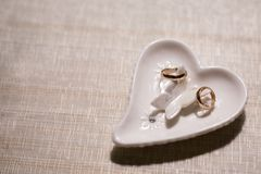 Two wedding rings on a support in the form of a heart on a light background stock photos