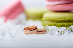 Two wedding rings and sweet macaroons Stock Photos