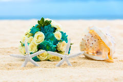 Two wedding rings with two starfish, wedding bouquet and a large. Shell on a sandy tropical beach. Wedding and honeymoon in the tropics Stock Images