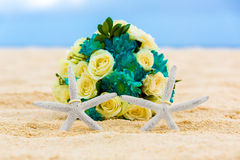 Two wedding rings with two starfish and wedding bouquet on a sandy tropical beach. Wedding and honeymoon in the tropics Stock Photography