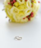 Two wedding rings and wedding bouquet Stock Images