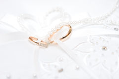 Two wedding rings on the wedding dress Stock Photography