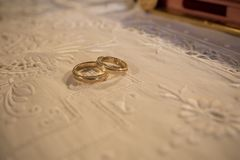 Two wedding rings upon a white cloth in preparation of church we. Stunning wedding stock photography from Zakynthos Greece! Exquisite wedding rings Stock Photo
