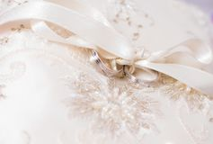 Two wedding rings on a white decorative cushion. Associated with a white decorative ribbon stock images