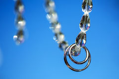 Two wedding rings in white gold on necklace of stones. Royalty Free Stock Images