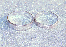Two wedding rings of white gold on silver glitter sparkle Stock Photos
