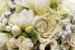 Two wedding rings on white roses bouquet. Close up photo of two wedding rings on white roses wedding bouquet Royalty Free Stock Image