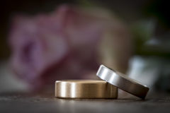 Two wedding rings on a wooden surface with rose Royalty Free Stock Photo