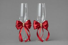 Two wedding wine glasses decorates with red bows. Two wedding wine glasses decorates with red silk bows stock images