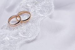 Two  weddings rings on white  fabric Stock Photos
