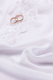 Two  weddings rings on white  fabric Stock Images