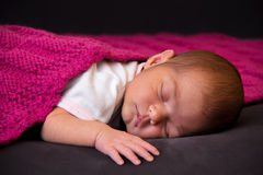 Two weeks old baby girl lying in bed Stock Image