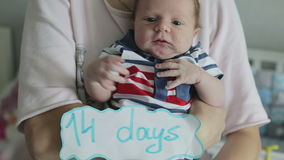 A two-weeks old boy being held. There is a notice saying 14 days . The child is moving his hands actively stock video