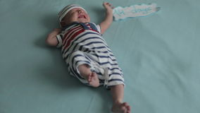 A two-weeks old boy crying. A two-weeks old boy in a cap and striped costume crying. He is moving has legs fast stock video
