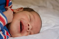 Two weeks old newborn baby boy smilin while sleeping on white quilt stock image
