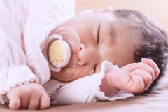 Two weeks old newborn baby girl sleeping with a pacifier. Close up portrait of a cute two weeks old newborn baby girl wearing soft pink knit clothes, sleeping Royalty Free Stock Photos