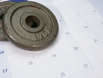Two weight plates. On a white and blue calendar Stock Images