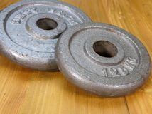 Two weight plates. On a wooden floor Stock Photography
