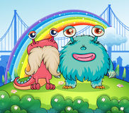 Two weird monsters and a rainbow in the sky. Illustration of the two weird monsters and a rainbow in the sky Royalty Free Stock Image