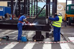 TIMISOARA, ROMANIA-11.26.2017 Two constructio workers wearing protective equipment weld on the ground with a welding machine a lar stock photography